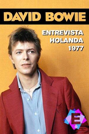 David Bowie con chaqueta roja sdelante de una pared naranja
