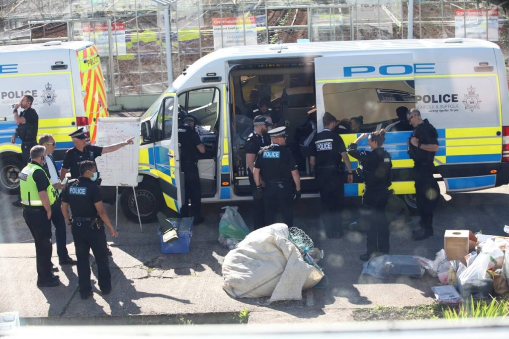 Police officers surround a police van and bags of confiscated personal belongings during a raid on the Animal Rebellion camp at g7