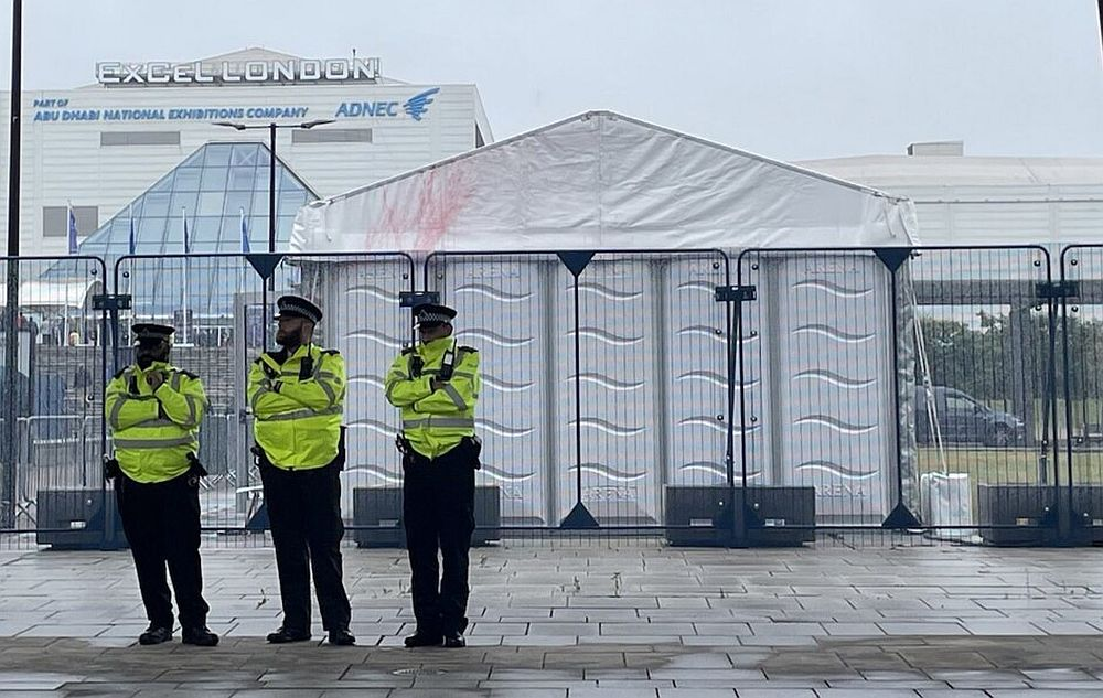 Three police officers stand in line outside the ExCel Centre, where the DSEi arms fair was taking place in early September 2021
