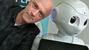 Lars Michael Sørensen læner sig op ad robot