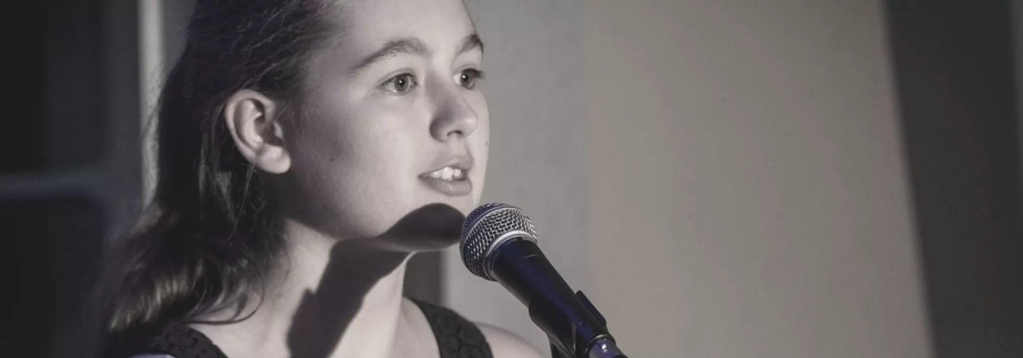 Poetry Slammerin steht am Mikrophon