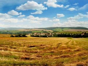 Sommerlandschaft mit blauem Himmel, Wolken, sanften Hügeln, Feldern, Wiesen und einem Dorf