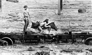 Zwei Männer mit Pferden in hüfttiefem Schlamm und Staub