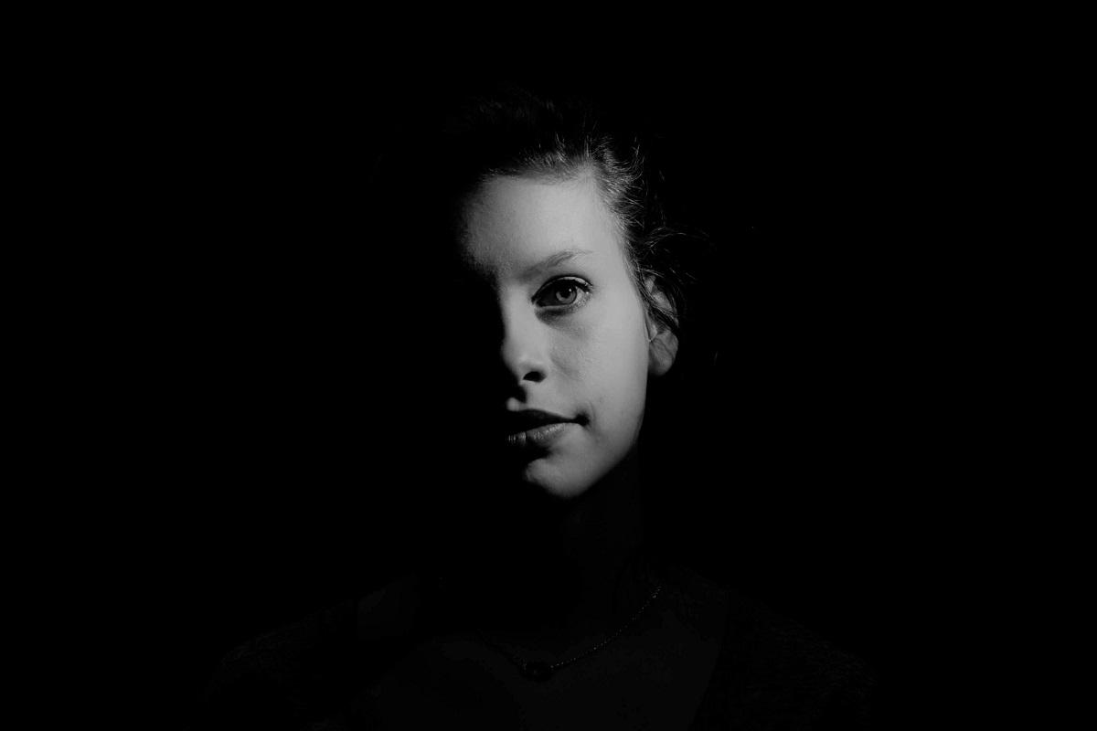 Ein Gesicht im Dunkeln ist nur teilweise erkennbar. (Foto: atc-commphoto, Unsplash)