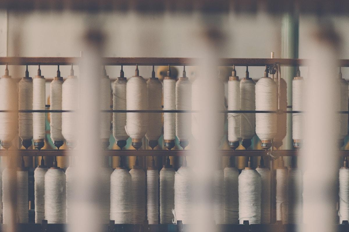 Verarbeitung von Baumwolle auf Spindeln. (Foto: Janko Ferlic, Unsplash.com)