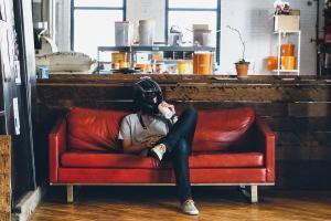 Ein Mensch mit Motoradhelm auf dem Kopf sitzt auf einem Sofa. (Foto: Ben Konfrst, Unsplash.com)