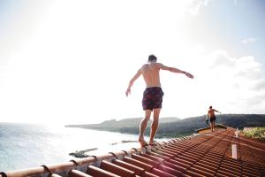 Ein Mann balanciert auf einem Dach. (Foto: Quinten de Graaf, Unsplash.com)