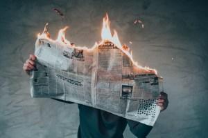 Leser mit brennender Zeitung. (Foto: Elijah O'Donell, Unsplash.com)
