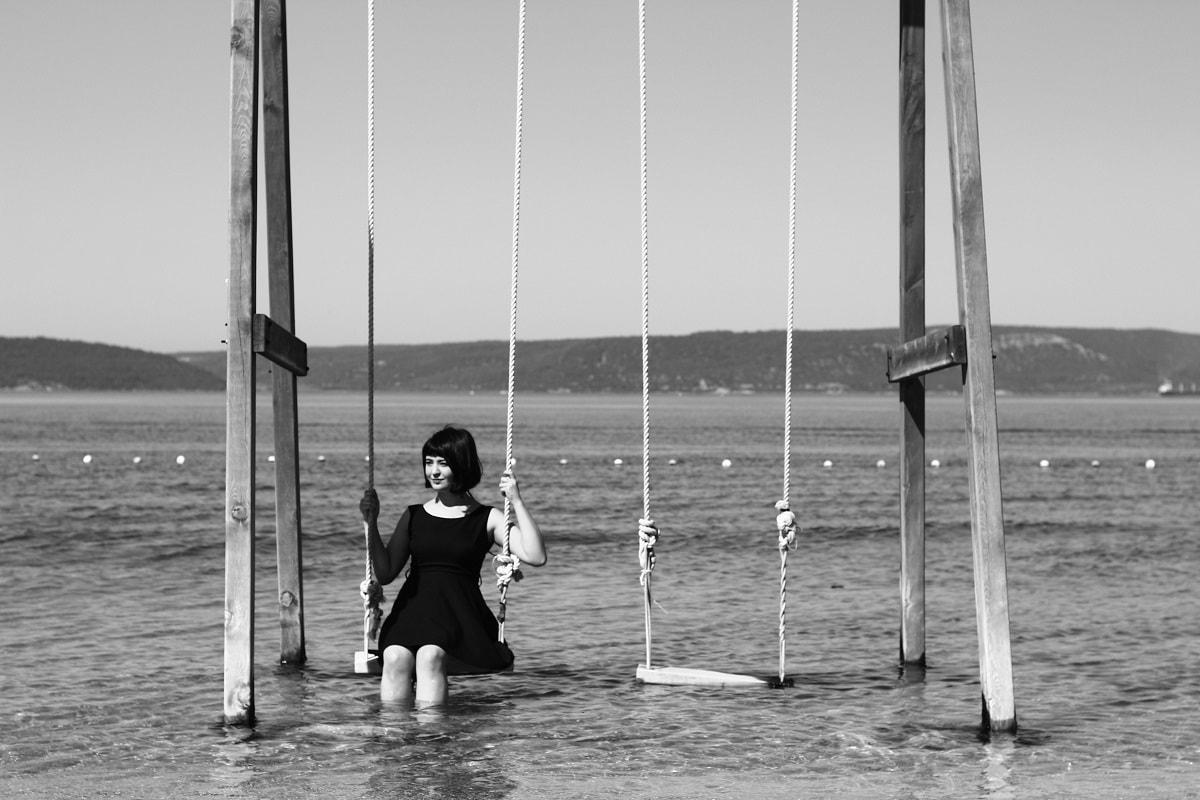 Frau auf einer Schaukel im Wasser. (Foto: Meric Tuna, Unsplash.com)