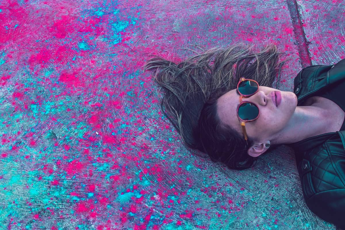 Eine Frau liegt auf einem mit roter und türkisfarbiger Flüssigkeit bespritzten Gehsteig. (Foto: Lucas Lenzi, Unsplash.com)