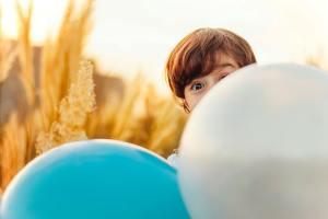 Ein Kind hinter Luftballons. Eltern haben eine besondere Verantwortung. (Foto :Ramin Talebi, Unsplash.com)