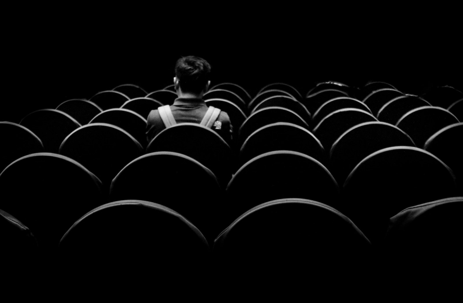 Dunkle Stellen gibt es auch beim Mythos 9/11. Eine Person sitzt in einem dunklen Saal. (Foto: Dibakar Roy, Unsplash.com)