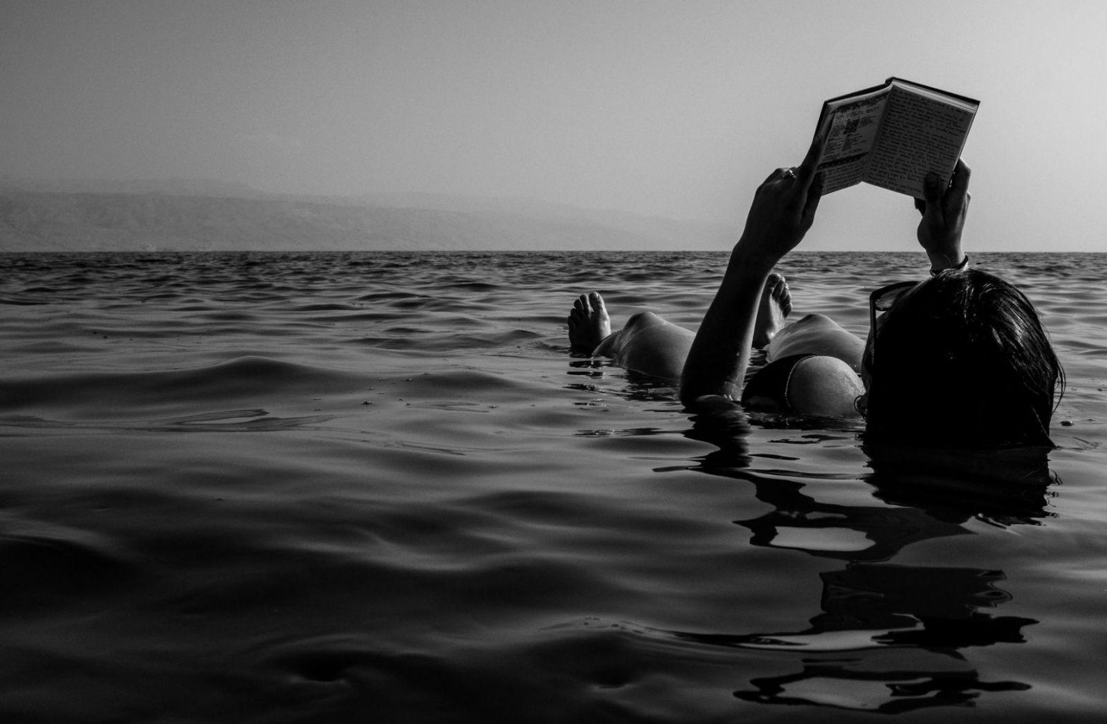 Eine Frau liegt im Wasser und Liest ein Buch. (Foto: Bruno Aguirre, Unsplash.com)
