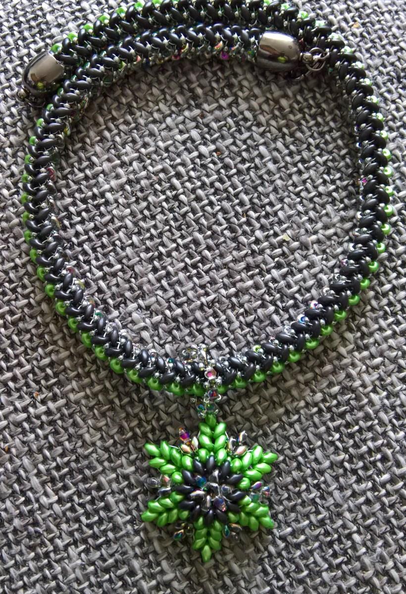Kette aus Superduo-Perlen, schwarz, grün und irisierend mit einem Stern als Anhänger.