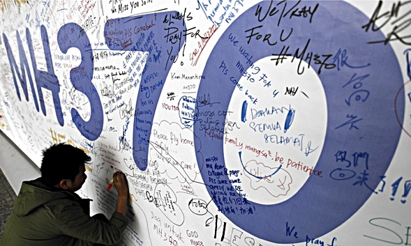 A man writes a message for passengers of Malaysian Airline flight MH370 on a banner at Kuala Lumpur International airport Photograph: Mak Remissa/EPA