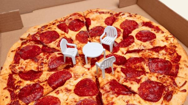 Kanada's Boston Pizza stellt drei kleine Stühle zum Tisch in der Mitte, jeder im Karton angelieferten grossen Pizza.