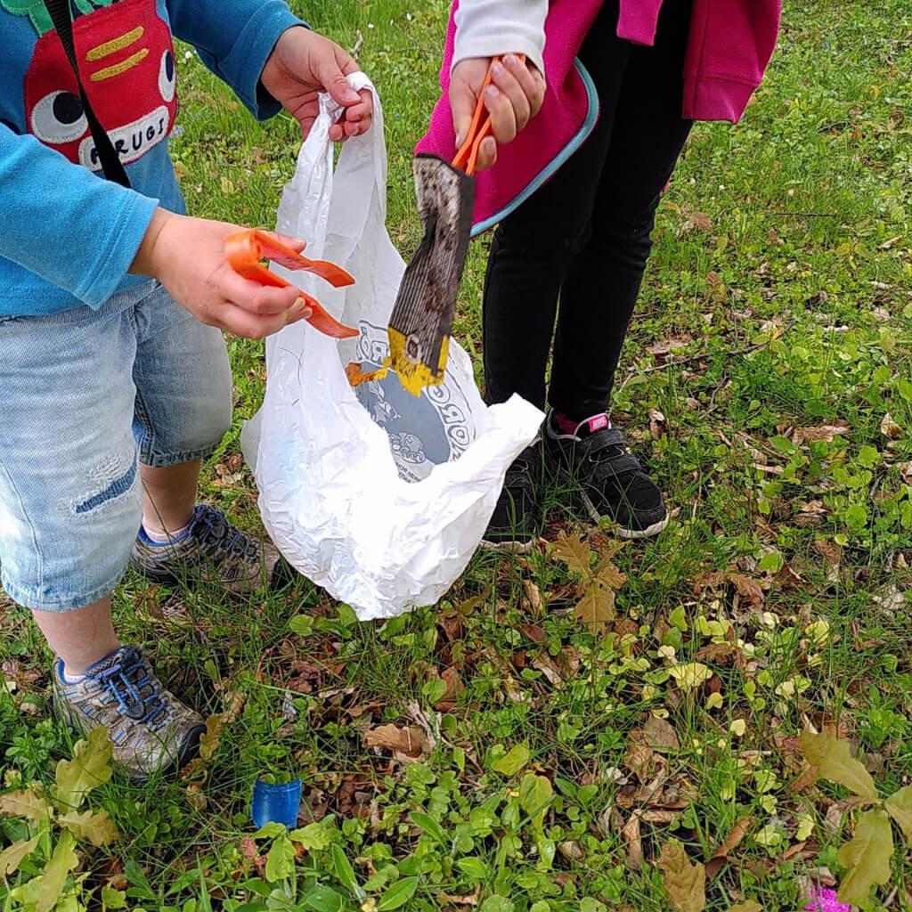 Kinder beim Müllaufsammeln auf einer Wiese