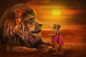 2 girls standing in front of a large lion. The one in front is holding her hand out to him while the other one peeks from behind her (the first one's) shoulder.