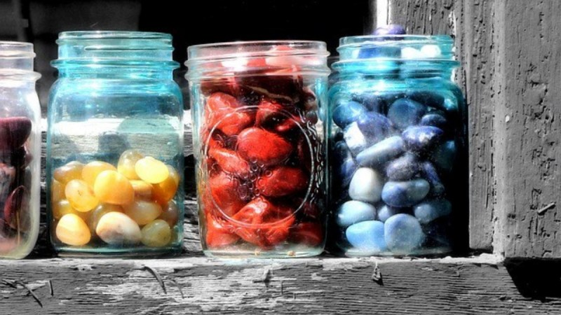 4 jars, the first of which is half cropped out. The second jar is half full of yellow stones, the third full of red stones and the fourth with blue stones.