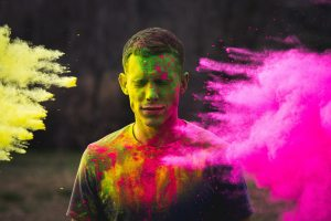 A man with his eyes closed being splashed with paint. A pink paint cloud appears on the right.