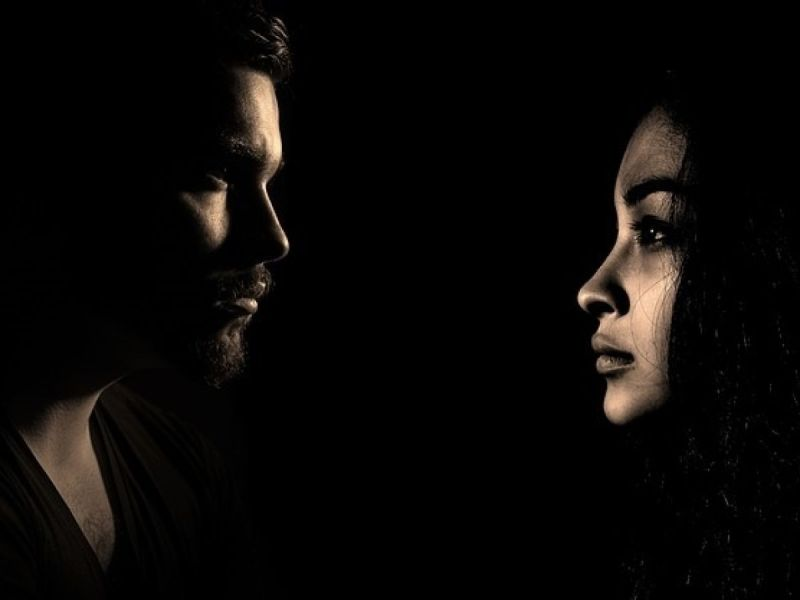 A dark picture of a man and a woman facing each other with their faces illuminated