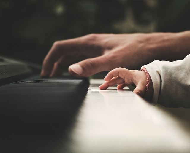 An adult and a child's hands on a piano.