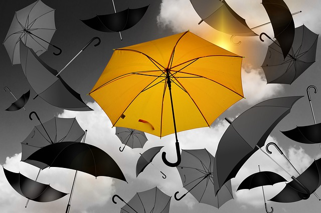 A yellow umbrella standing out from a bunch of black and gray umbrellas