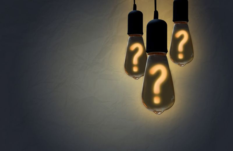 Three lightbulbs with bright question marks on them.