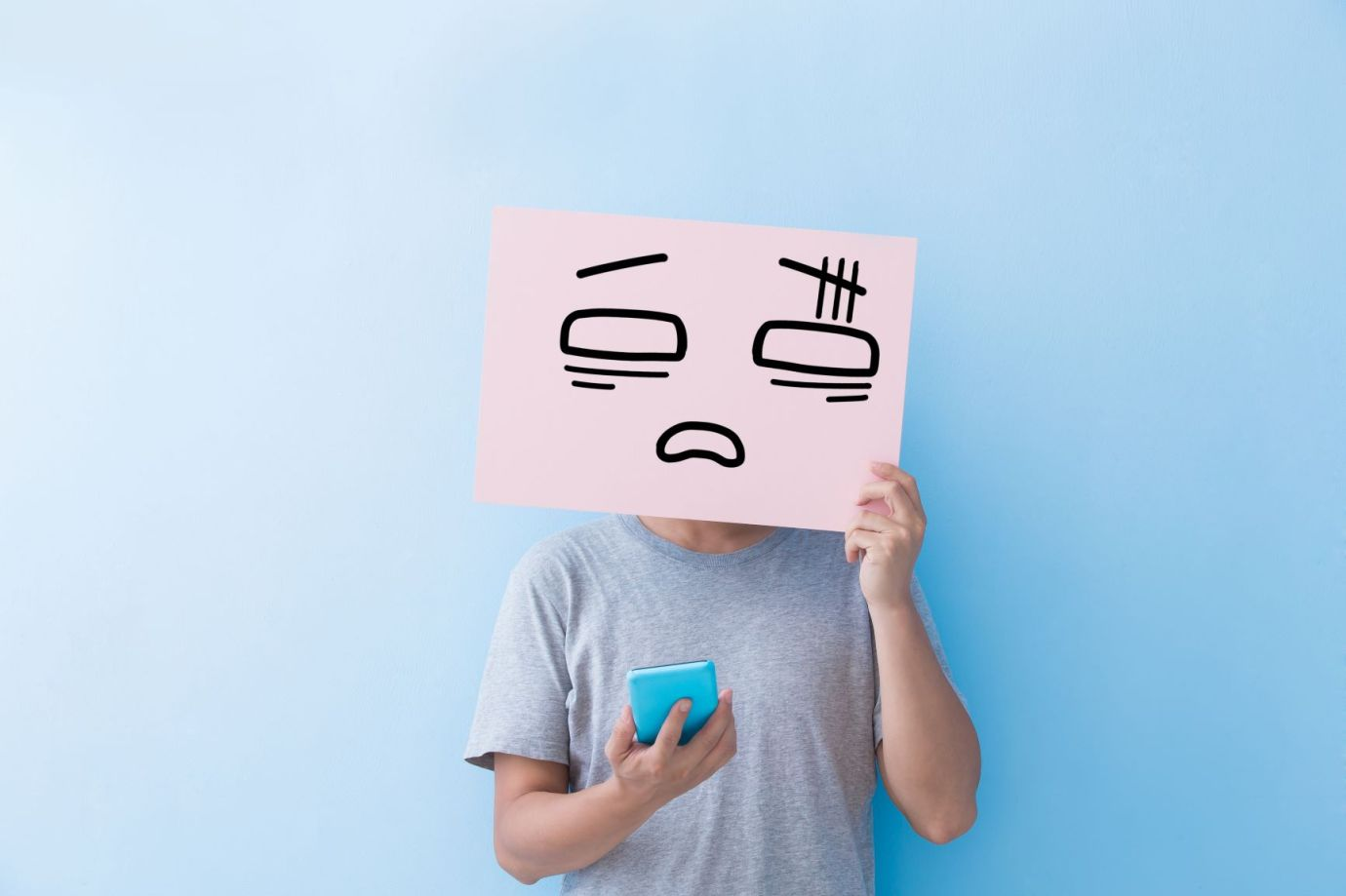 A guy holding up a poster in front of their face with a sad emoticon on it, while holding their phone.
