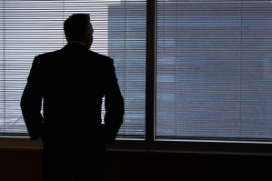 Man in a suit looking out an office window