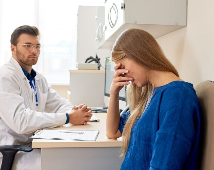 White woman patient looking sad sitting by a white male doctor looking at her.