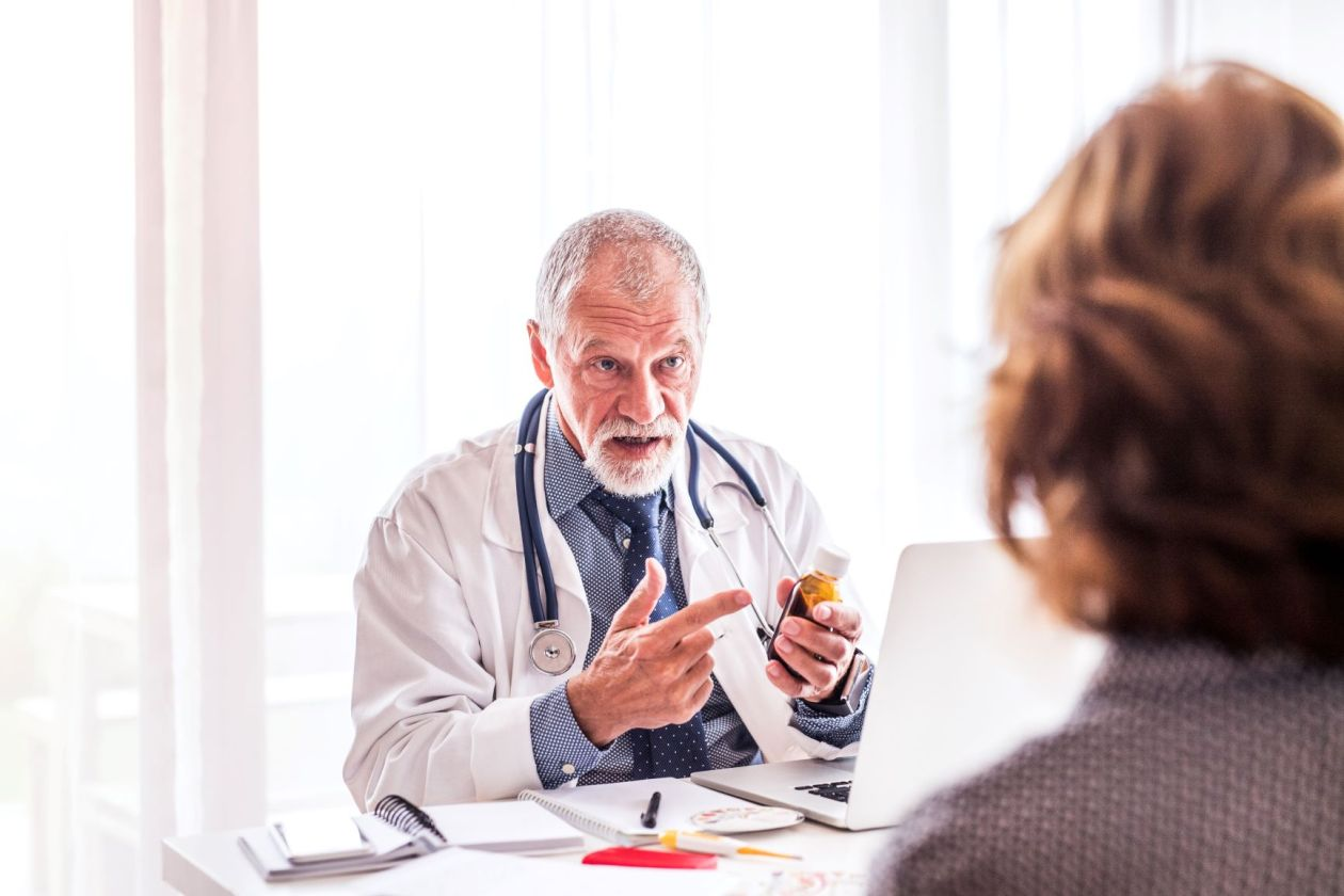 White old guy doctor talking to a patient.