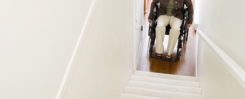 Black woman in a wheelchair looking up a set of stairs in a house.