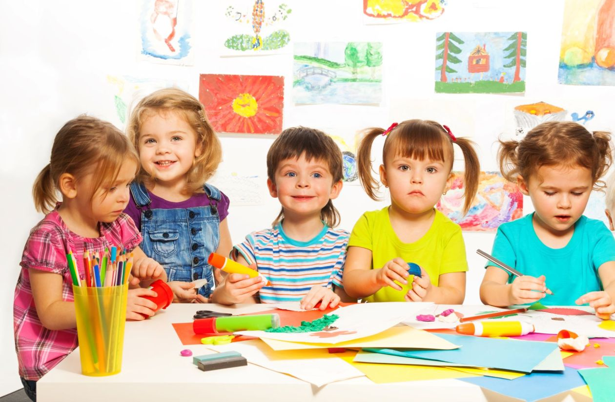 White children doing crafts in therapy looking at the camera.