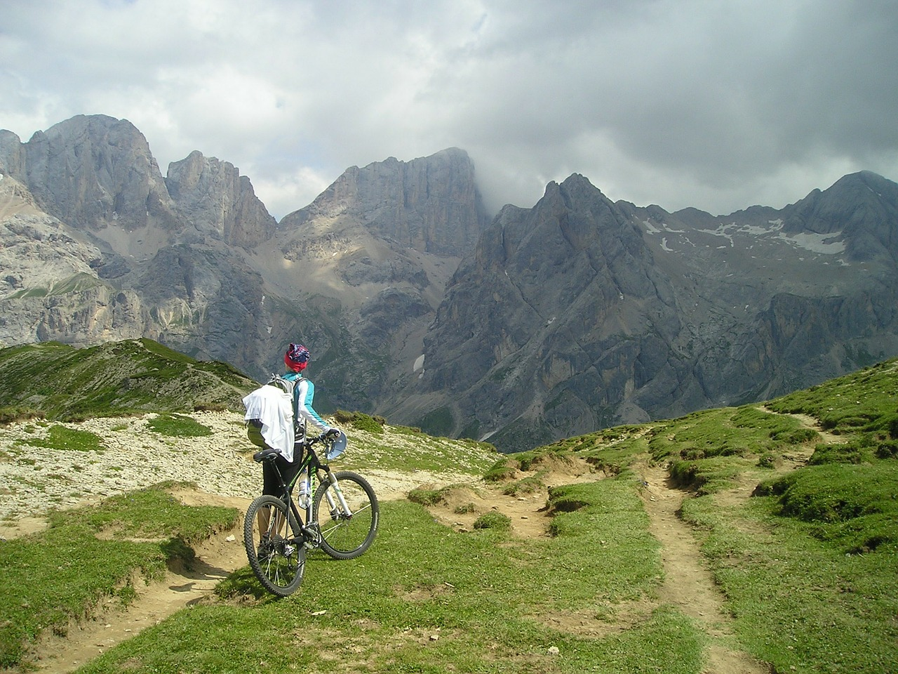 Cyclist holding a bike, standing and looking at a mountain in front of them, facing away from the camera.