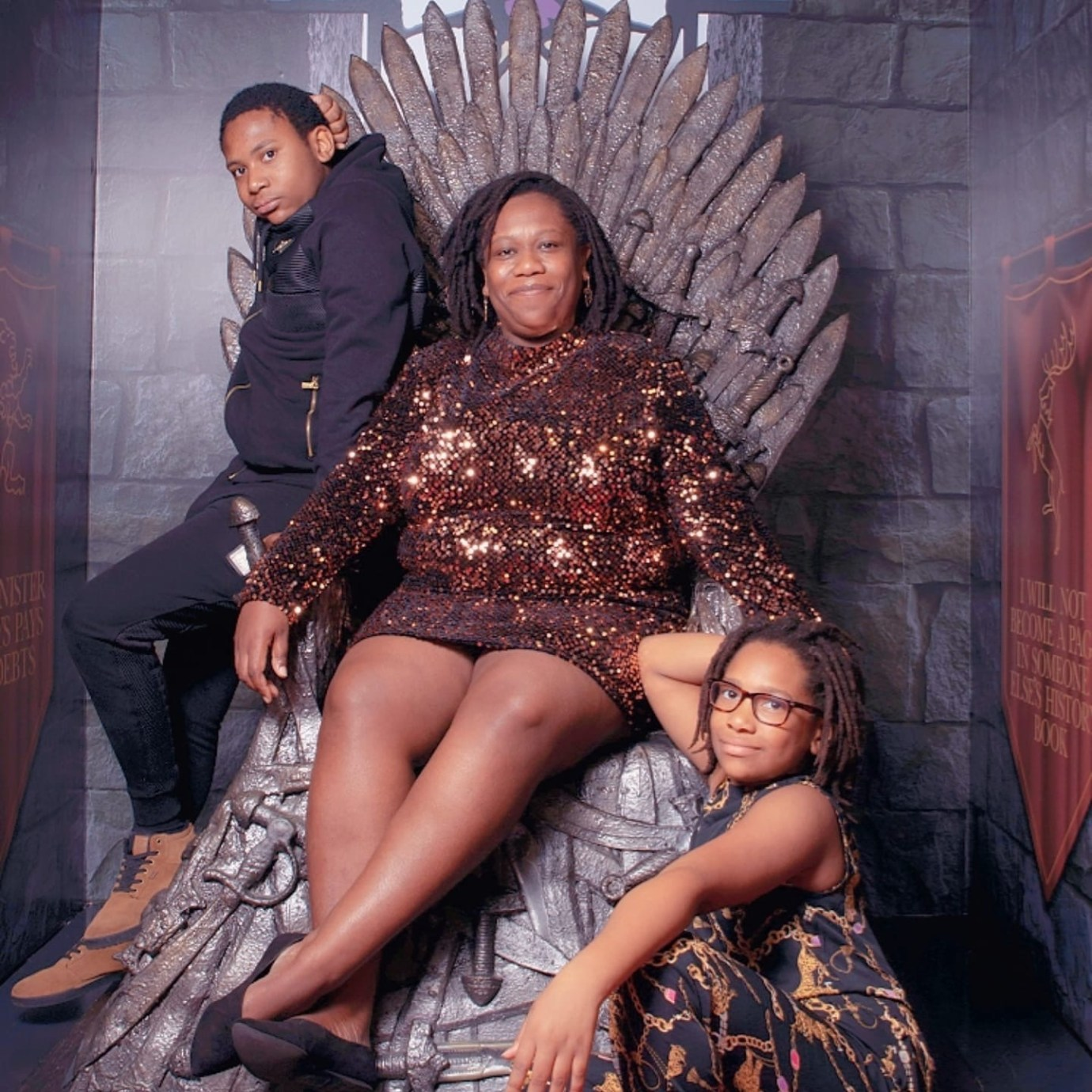 Beautiful black woman sits on throne like chair with her two children around her.