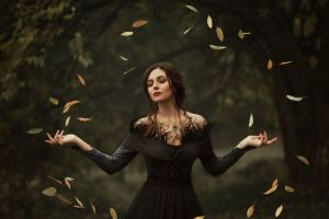 A beautiful, magical autistic woman in a gothic style dress conjures leaves to circle around her. Her eyes are closed