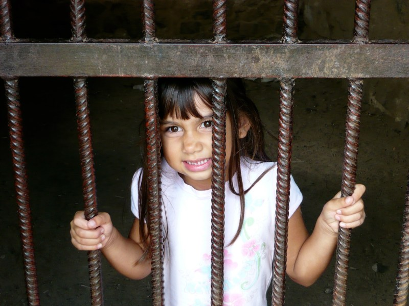Six year old girl holds onto prison bars from inside a cell