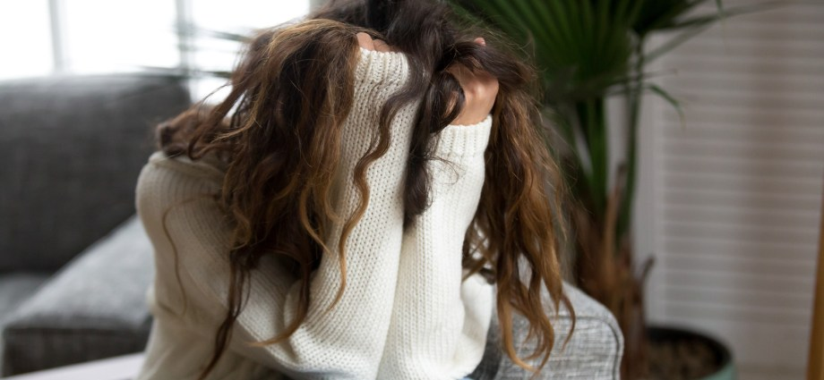 Young woman has her face buried behind her arms, with her arms and hair completely hiding her face. This image is meant to convey an autistic person struggling with addiction. Autism.