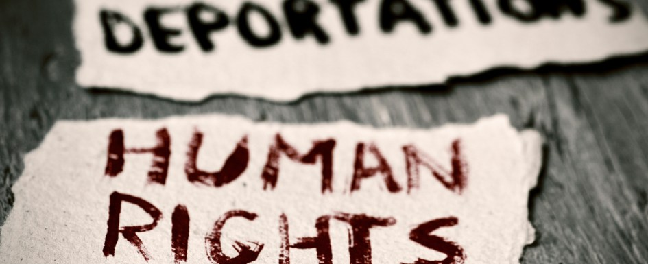 closeup of some pieces of paper with the text human rights and stop deportations handwritten in them on a rustic wooden surface