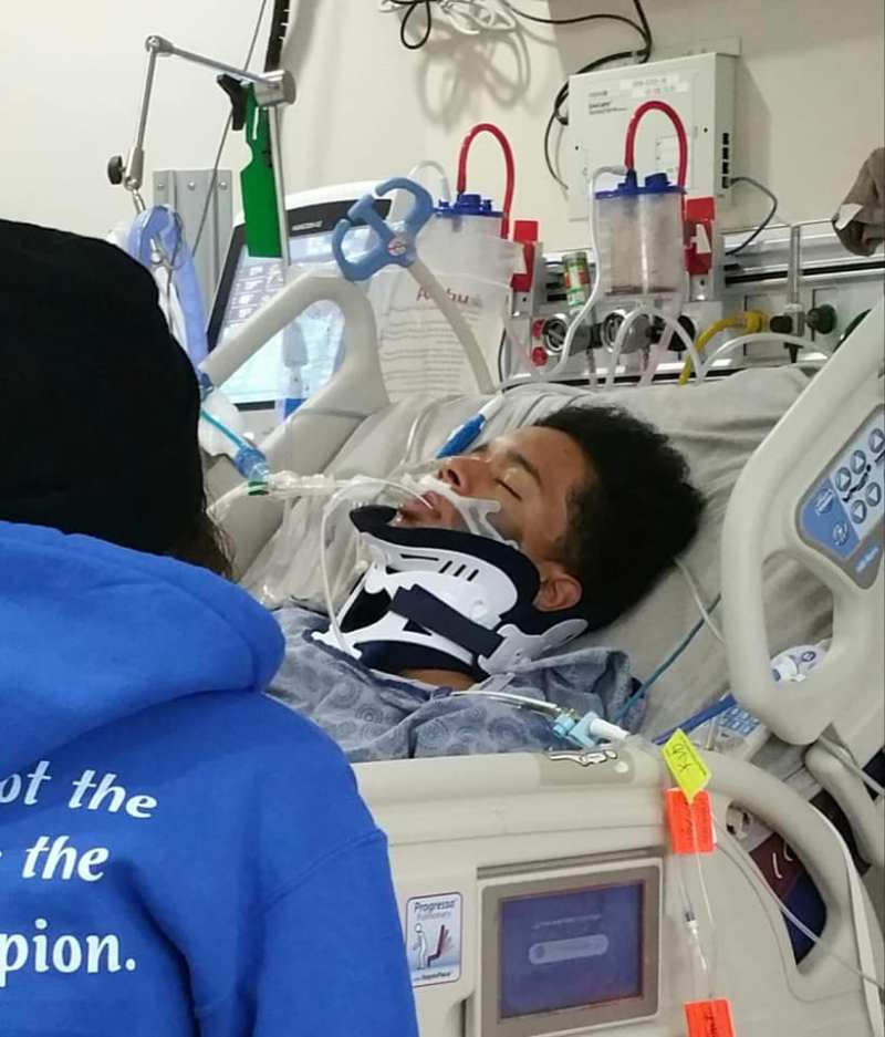 photo of a young Black adult in a hospital bed, eyes closed, with a neck brace and tubing around him.