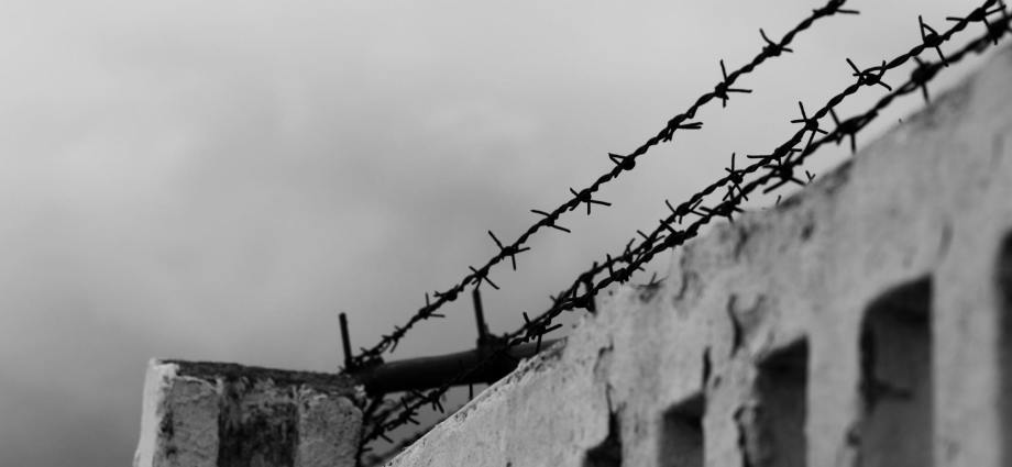 Barbed wire at the top of a cement fence
