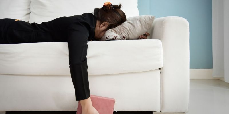A female appearing person who appears to be asian is lying face down on a white couch, a book in hand, glasses off to the side. She ooks exhausted and symbolizes autistic burnout in autism adulthood.