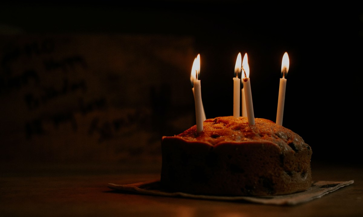 birthday cake over a table in dark environment