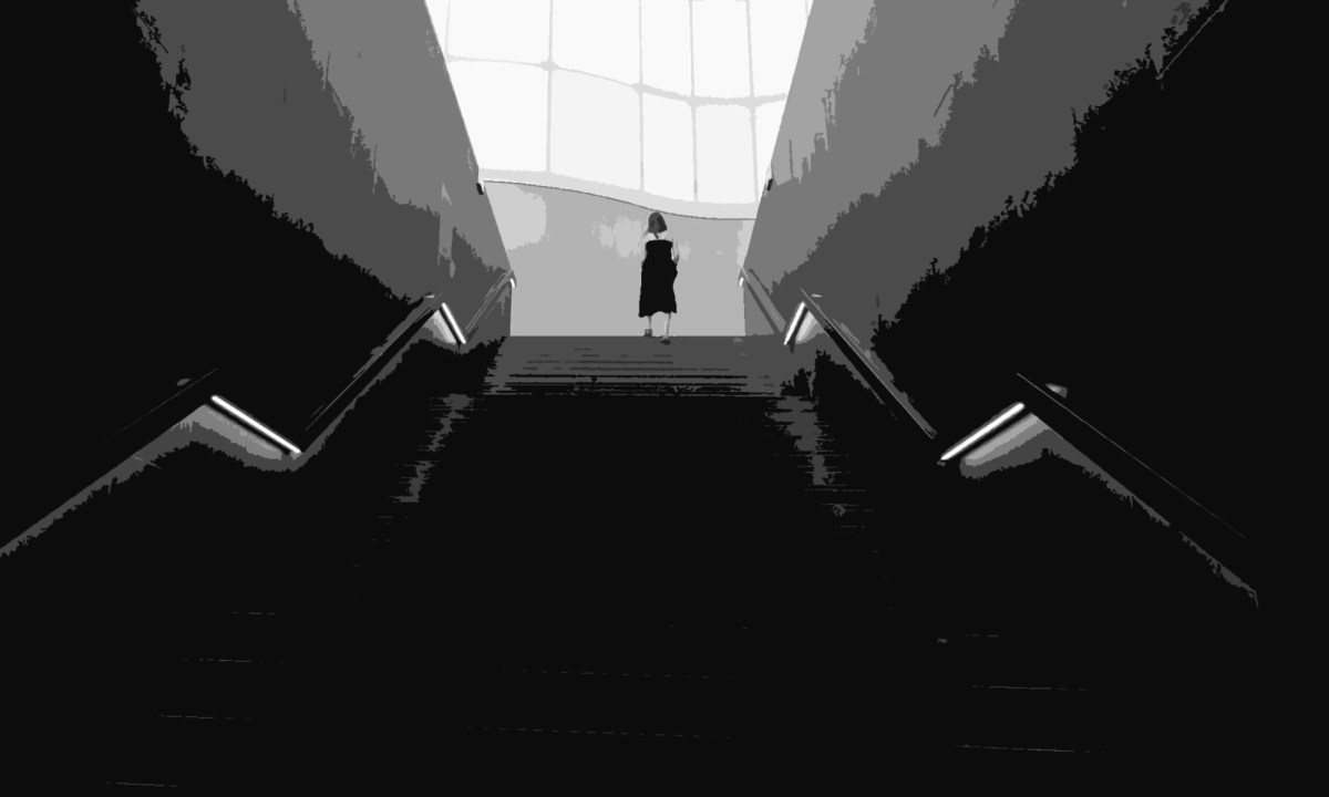 woman at the top of the stairs in a dark environment