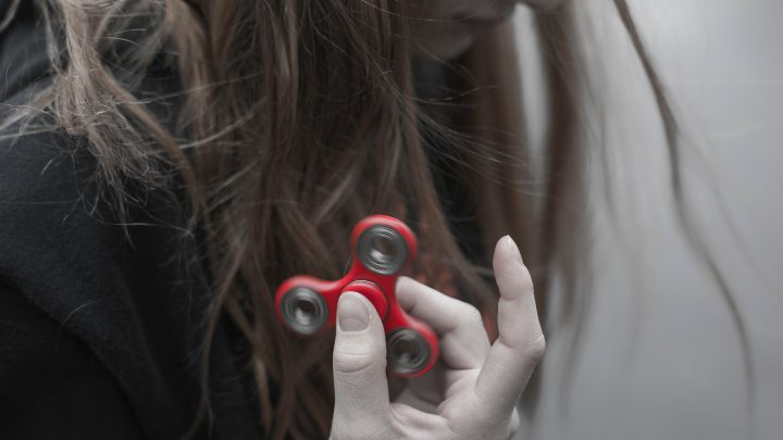 Adult woman profile holding red fidget spinner between two fingers.