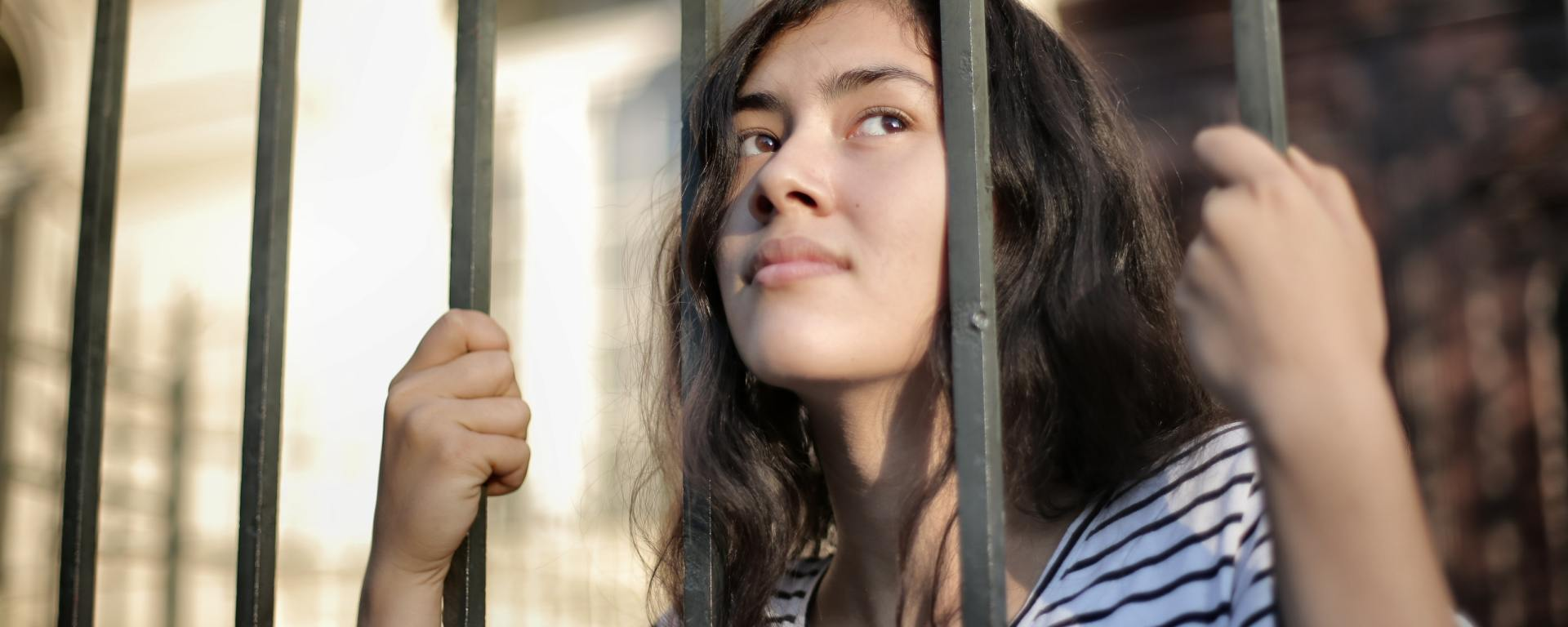 A human with long hair and a v neck tshirt is behidn bars (a fence) outdoors, placing their face through the hole of the bars
