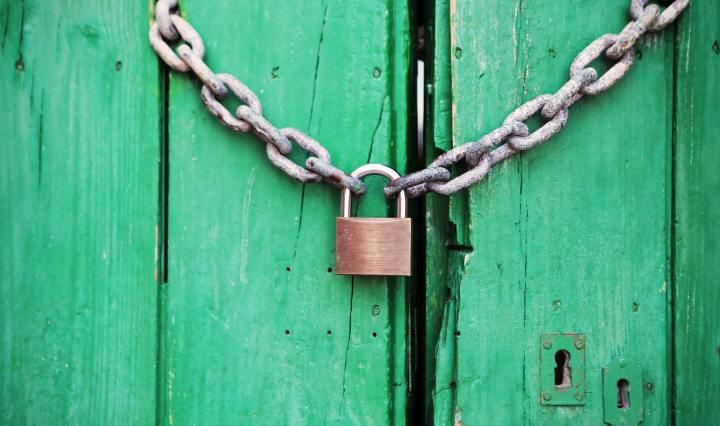 A Green Door is locked by a chain with a gold padlock