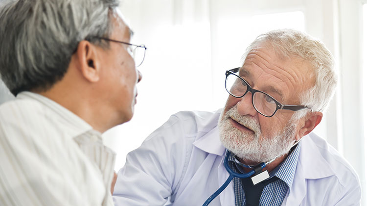 Senior male doctor talking with senior Asian male patient