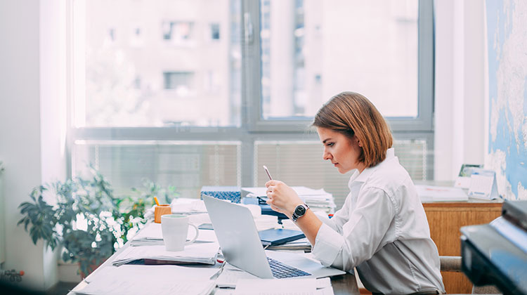 Woman in office working on computer and phone